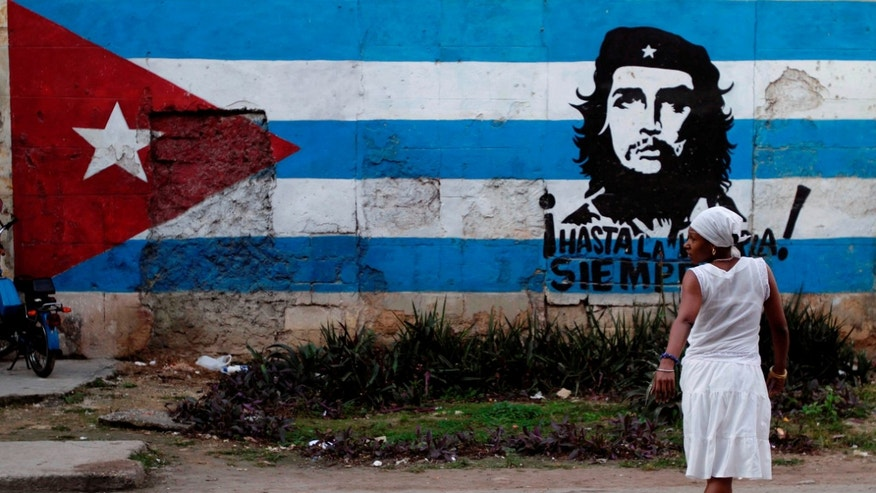 "A santera looks back while crossing the street where a wall is covered with a mural of the Cuban flag and an image of Cuba's revolutionary hero Ernesto ""Che"" Guevara in Havana, Cuba, Friday Jan. 27, 2012. After economic reforms by President Raul Castro were endorsed by the communist congress in mid-2011, the Communist Party of Cuba (PCC) is preparing to hold a party conference this weekend. (AP Photo/Franklin Reyes)"