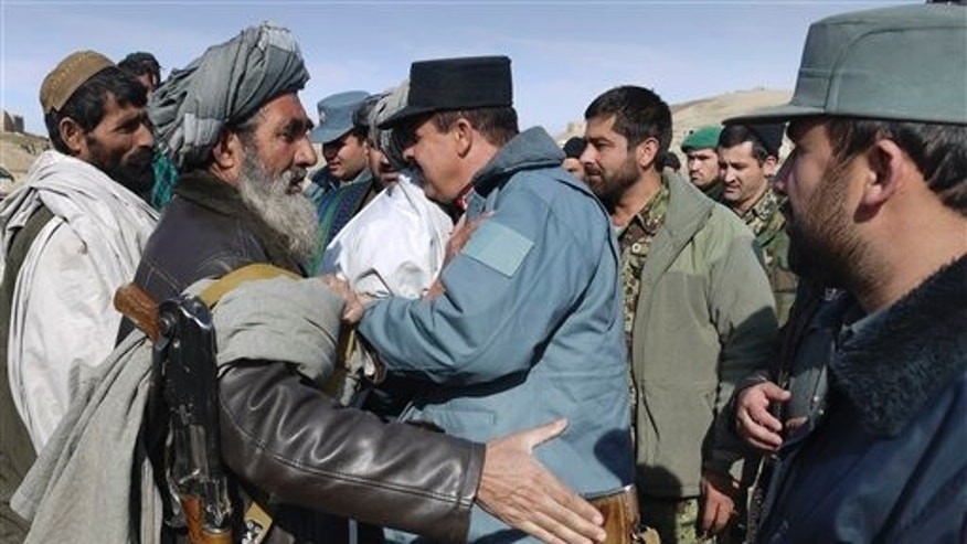 Jan. 24, 2012: A former Taliban militant, left, shakes hands with a police official during a joining ceremony with the Afghan government in Baghlan, north of Kabul, Afghanistan.