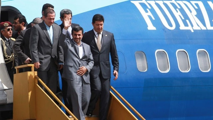 January, 12, 2012: Iran's President Mahmoud Ahmadinejad waves as he exits a plane upon arrival to an air force base in Quito, Ecuador.