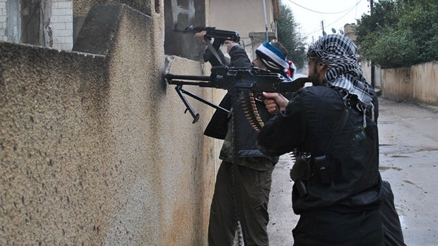 Jan. 31: Syrian rebels take their position behind a wall as they fire  their guns during a battle with the Syrian government forces, at Rastan area in Homs province, central Syria.