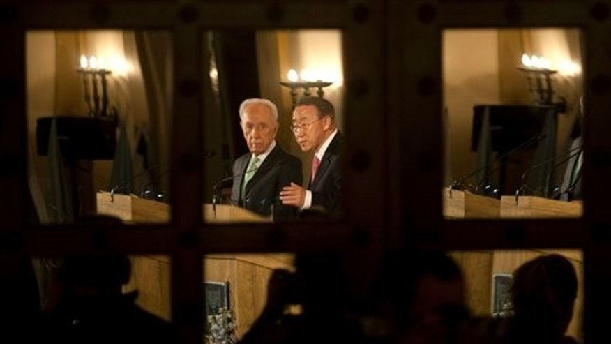 Feb. 1: Israel's President Shimon Peres, left, and United Nations Secretary General Ban Ki-moon are seen reflected in a door's mirror as they speak during a joint news conference at a Jerusalem hotel.