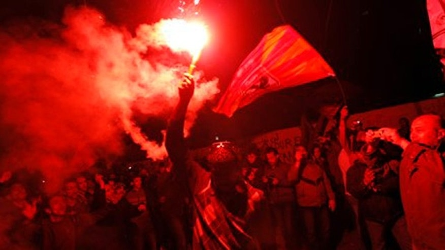 Feb. 2, 2012: An Egyptian waves a flare as others chant slogans during a protest in Tahrir Square in Cairo, Egypt.