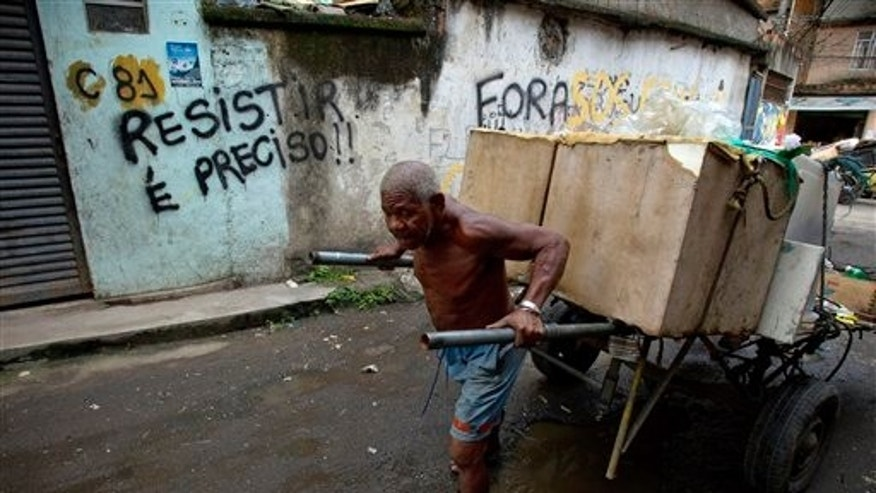Jan. 31: A man pushes a cart with goods to recycle past a graffiti that reads in Portuguese 'We must resist' in the Favela do Metro shantytown in Rio de Janeiro, Brazil.