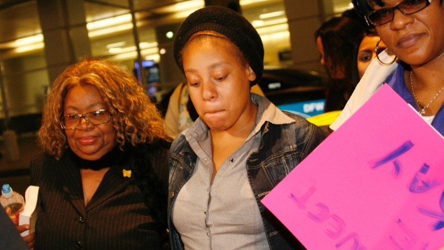 Jakadrien Turner, age 15, center, walks with her grandmother Lorene Turner, left, and mother Johnisa Turner, right, all of Dallas, at DFW Airport in Fort Worth, Texas, on Friday Jan. 6, 2012. (AP Photo/Mike Fuentes)