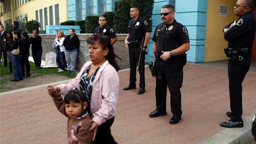 Los Angeles Unified School District police guard the front door of Miramonte Elementary school as parents protest outside in Los Angeles on Monday, Feb. 6, 2012. (AP Photo/Damian Dovarganes)