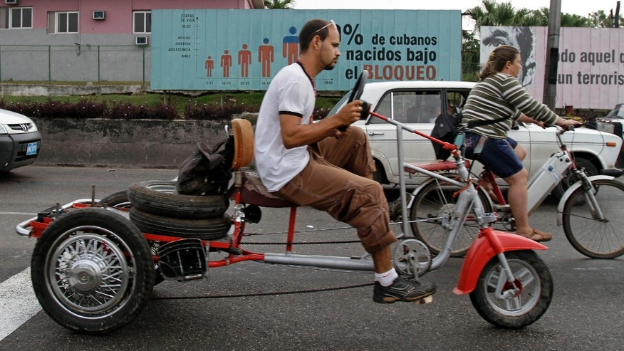 "Commuters ride past a billboard that reads in Spanish; ""70 percent of Cubans have been born under the Embargo,"" in Havana, Cuba, Tuesday Feb. 7, 2012. The United States economic embargo on Communist-run Cuba turned 50 on Tuesday. (AP Photo/Franklin Reyes)"