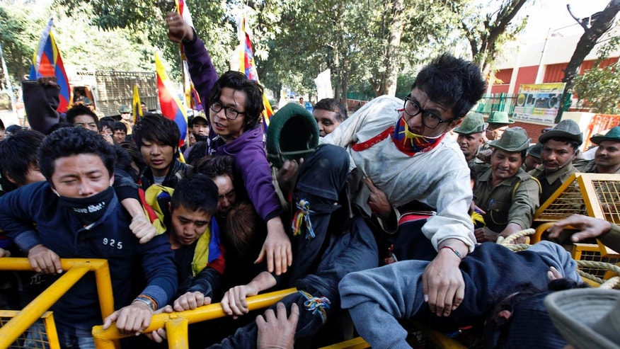 Feb. 8, 2012: Tibetan exiles shout slogans as they attempt to break a police barricade near the Chinese Embassy at a protest against the Chinese government, in New Delhi, India.