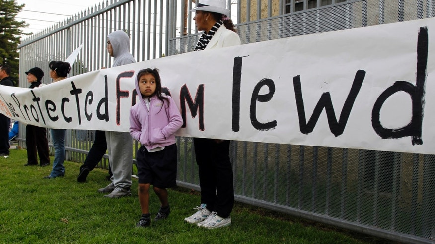 Ivis Urbina, right, with her granddaughter Alexa Agillon, 6, protest with others outside Miramonte Elementary school in Los Angeles Monday, Feb. 6, 2012.