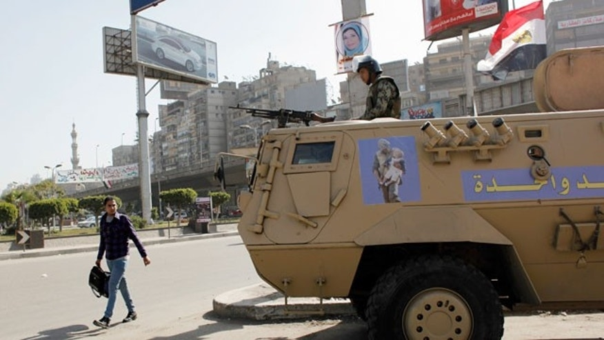 "Feb. 11, 2012: An Egyptian man passes by an army patrol with a soldier on top of an armored vehicle flying the national flag and a sticker on the body with Arabic that reads ""the army and the people are one hand,"" during a general strike in Cairo, Egypt."