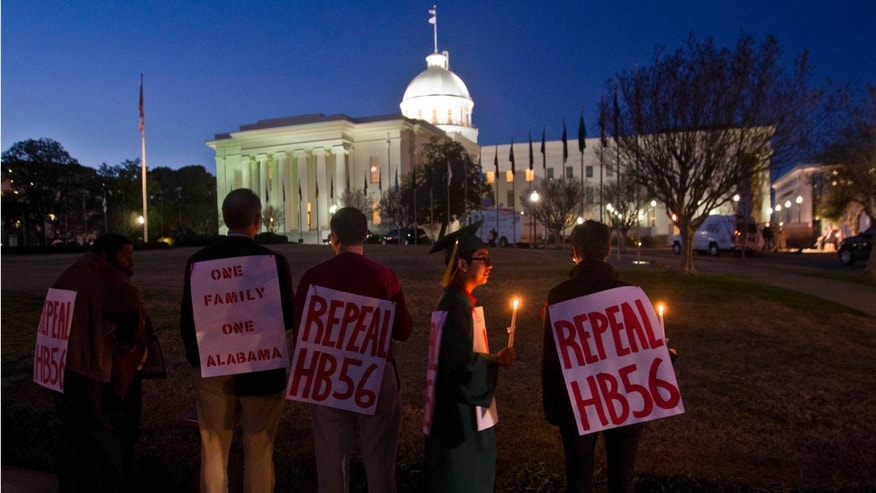 About a dozen protestors gather outside the Capitol to demonstrate against Alabama's immigration law prior to Gov. Robert Bentley's State of the State address to a combined session of the Alabama Legislature in Montgomery, Ala., on Feb. 7, 2012. (AP Photo/Dave Martin)