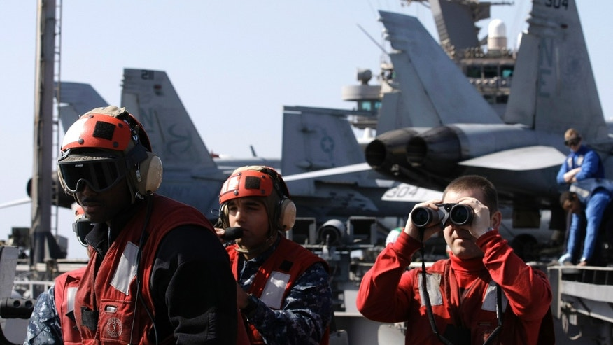 Feb. 14, 2012: Crew look out over the Arabian sea from the flight deck of the Nimitz-class aircraft carrier USS Abraham Lincoln (CVN 72) in the Strait of Hurmuz.