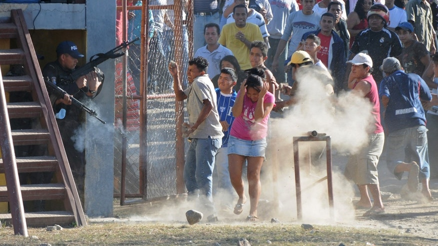 Inmates' relatives clash with police outside a prison after a deadly fire in Comayagua, Honduras, 90 miles (140 kilometers) north of the capital, Tegucigalpa, Honduras, Wednesday Feb. 15, 2012. At least 300 inmates were killed and 21 are injured, according to authorities. (AP Photo/Fernando Antonio)