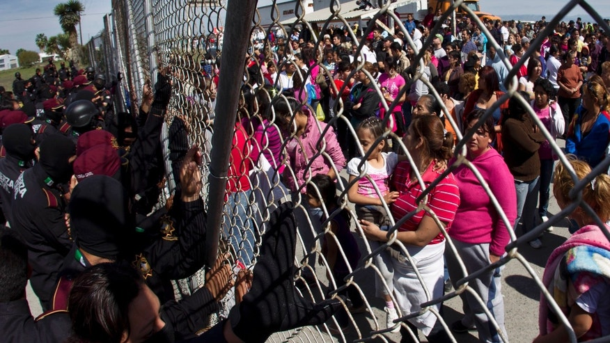 Police hold back the relatives of inmates outside the Apodaca correctional state facility as they try to get past the gates in Apodaca on the outskirts of Monterrey, Mexico, on Sunday. (AP Photo/Hans Maximo Musielik)