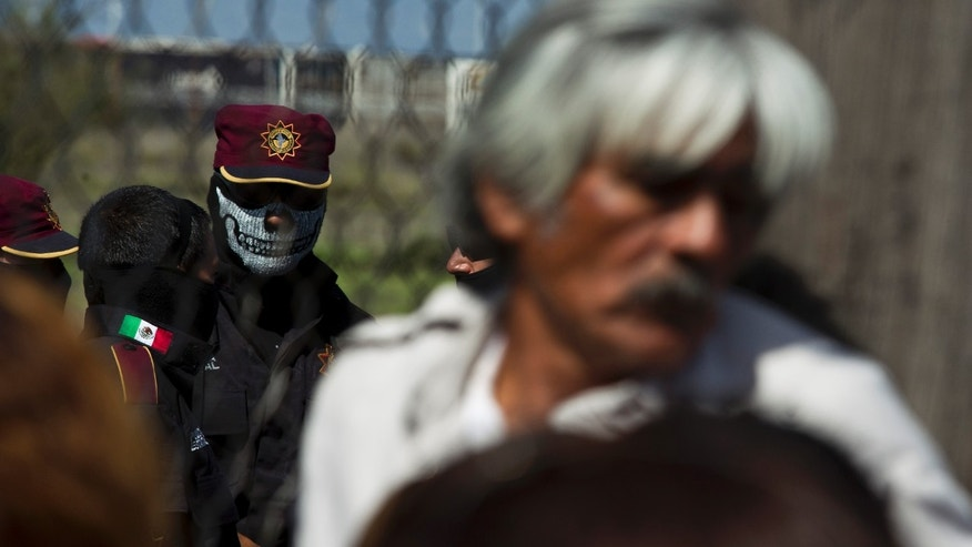 A state police officer wearing a face mask stands behind the fence as relatives of inmates wait for news after a prison riot at Apodaca correctional state facility in Apodaca on the outskirts of Monterrey, Mexico, on Sunday. (AP Photo/Hand Maximo Musielik)