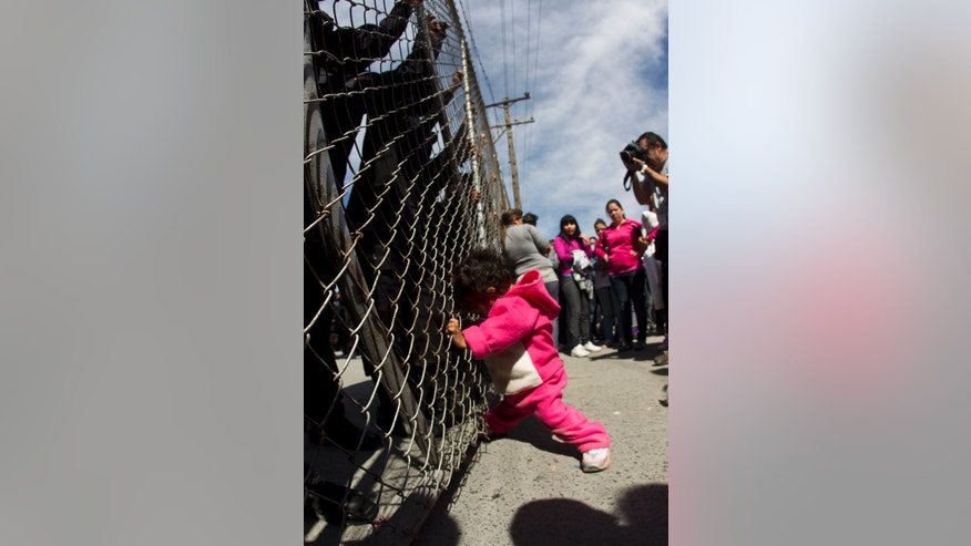 A child yells out for her father as she pushes on a gate where police stand on the other side after her mother and other adults pushed the gates in an attempt to get past state police at the Apodaca correctional state facility in Apodaca on the outskirts of Monterrey, Mexico on Sunday. (AP Photo/Hans Maximo Musielik)