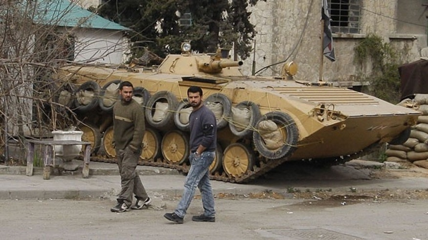 Feb. 15, 2012: In this photo taken on a government-organized tour for the media, Syrian citizens pass by a Syrian government army tank, in one of several suburbs of Damascus that saw heavy fighting between troops and defectors before Assad's forces retook the areas in late January, in Harasta suburb, Damascus, Syria.