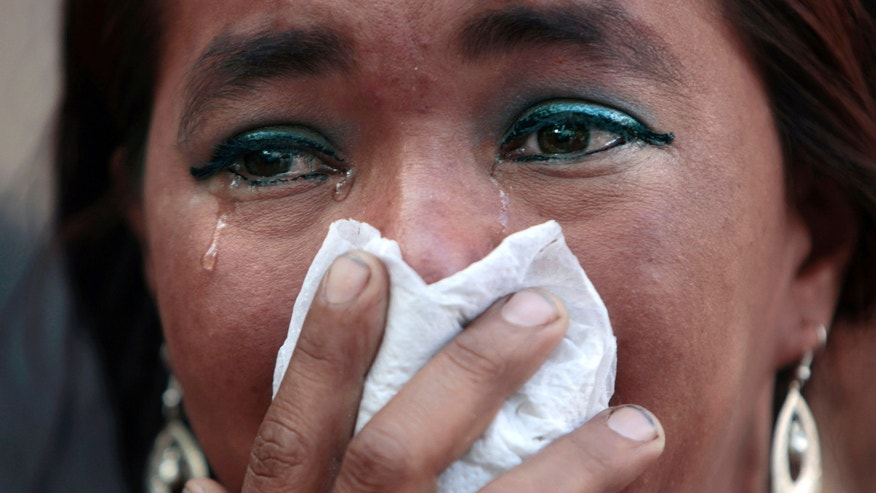 A woman, relative of an inmate killed during last week's prison fire, cries while she and others inspect bodies looking for relatives at the morgue in Tegucigalpa, Honduras, Monday, Feb. 20, 2012. Relatives entered the restricted area of the morgue, clashing with police and army, as forensic experts try to identify the hundreds of prison inmates that died in last week's Comayagua deadly prison fire. (AP Photo/Esteban Felix)