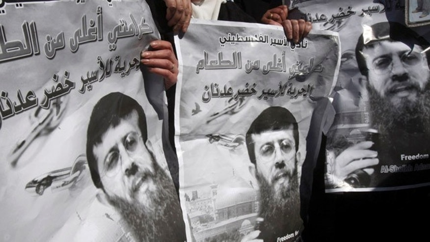 Feb. 21: Palestinians hold posters during a demonstration in solidarity with Islamic Jihad member Khader Adnan, who has been on hunger strike for two months, in the West Bank city of Nablus.