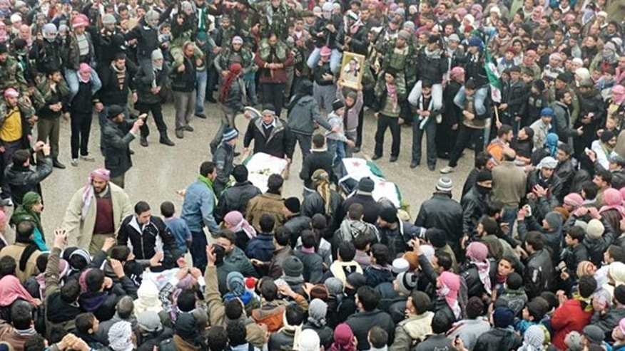 In this undated citizen journalism image provided by the Local Coordination Committees in Syria and accessed on Feb. 8, 2012, mourners gather around the bodies of people allegedly killed by Syrian government forces, during a funeral procession in Maarat al-Noman, Idlib province, Syria.