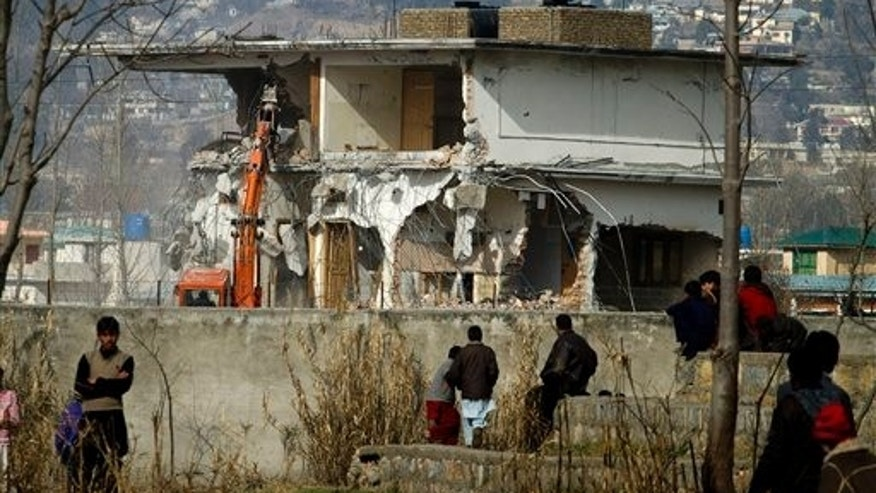 Feb. 26, 2012: Local residents watch as authorities use heavy machinery to demolish the compound of Usama bin Laden in Abbottabad, Pakistan. Pakistan was more than halfway done Sunday demolishing the three-story compound where bin Laden was killed by U.S. commandos last May, erasing a concrete reminder of a painful and embarrassing chapter in the country's history.