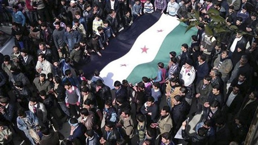 In this Feb. 24, 2012 citizen journalism image provided by the Local Coordination Committees in Syria and accessed on Saturday, Feb. 25, 2012, anti-Syrian regime demonstrators carry a large Syrian revolution flag during a demonstration, in Damascus, Syria.