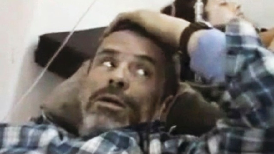 Feb. 22: file image from amateur video made available by Shaam News Network purports to show Paul Conroy of the Sunday Times, laying wounded, in a makeshift clinic in Homs.