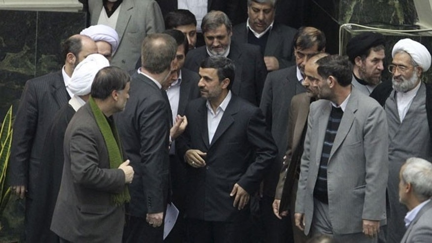 Feb. 1, 2012: In this photo released by the official website of the Iranian President's office, Iranian President Mahmoud Ahmadinejad, center, arrives at the parliament to deliver the new year's budget, as he is surrounded by lawmakers, in Tehran, Iran.