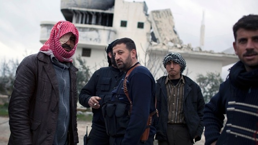 Feb. 28, 2012: Free Syrian Army soldiers gather outside a house destroyed in fighting against President Assad's forces in Sarmin.
