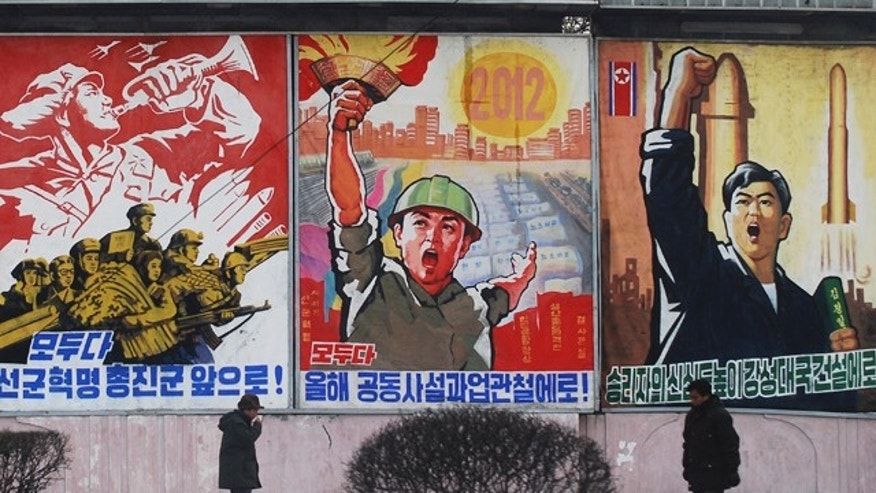 "In this Feb. 11, 2012 photo, residents walk past posters with popular slogans illustrating North Korea's main policies, on a street in Pyongyang, North Korea. From left to right, they read ""Let's march toward a military first revolution,"" ""Let's accomplish the tasks laid out in this year's joint new year's editorial,' and ""Devote the victors' hearts to the building of a strong nation."""