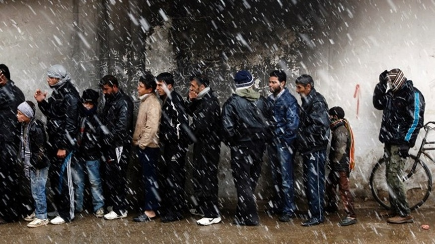March 1: Men wait to buy bread in front of a bakery shop during winter in Al Qusayr, a city in western Syria.