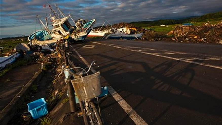 July 24, 2011: In this file photo an abandoned bicycle rests on a road partially blocked by ships that washed ashore in the town of Namie, inside the 12-mile exclusion zone around the Fukushima Dai-ichi nuclear plant, in northeastern Japan.