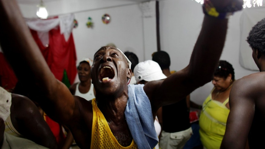 In this Dec. 4, 2009 photo, a man sings during a Santería ceremony in honor of St. Barbara in Santiago de Cuba, Cuba. (AP Photo/Javier Galeano)