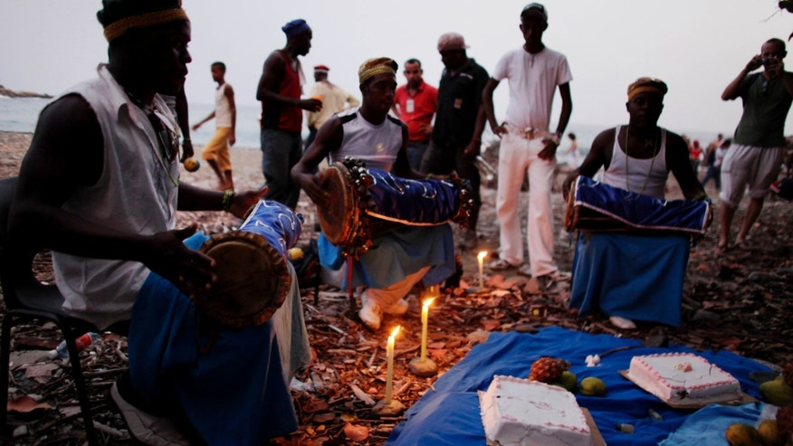 In this July 8, 2009 photo, drummers play and sing during a Santería ceremony in honor of the ocean goddess Yemayá at an annual Caribbean festival in Santiago de Cuba, Cuba. (AP Photo/Javier Galeano)
