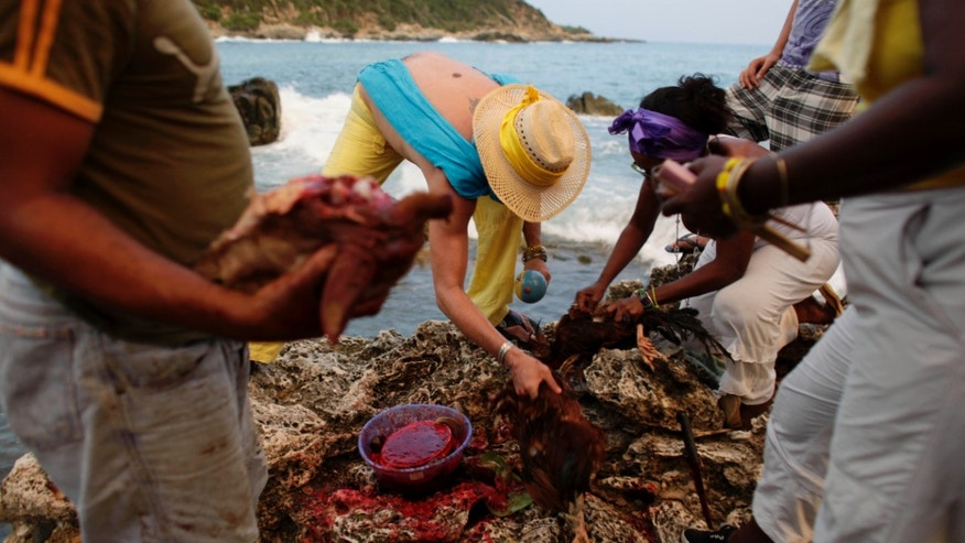 In this July 8, 2009 photo, people sacrifice a rooster and goat during a Santeria ceremony in honor of the ocean goddess Yemayá at the annual Caribbean Festival in Santiago de Cuba, Cuba. (AP Photo/Javier Galeano)