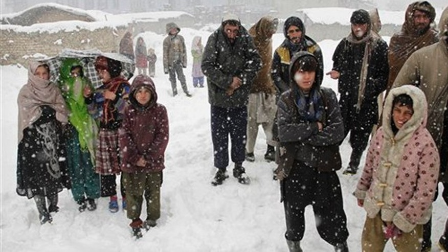 FILE: Afghans wait to receive blankets and winter jackets from Welthungerhilfe, a German NGO, during a snow fall at a camp for internally displaced people in Kabul.
