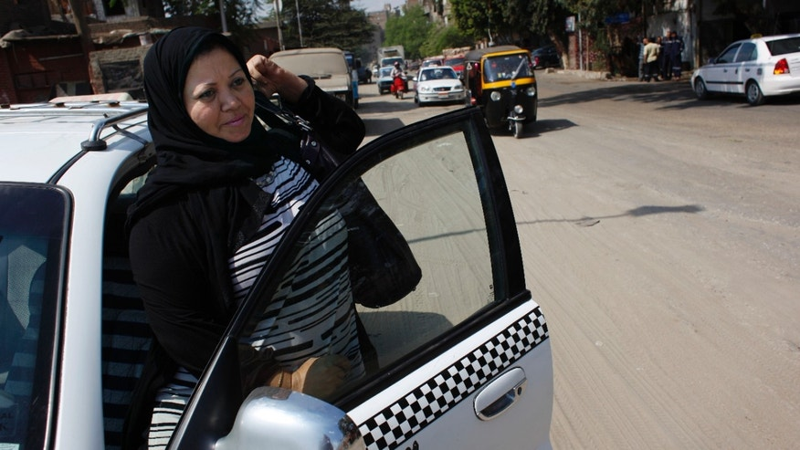 Oct. 3, 2011: Egyptian woman taxi driver Nadia Abdel-Gaber exits her taxi to take a break during her work day in Cairo, Egypt. Abdel-Gaber frequently gets double-takes from customers who hail her cab. Driving a cab is considered a man's work in conservative Egypt.