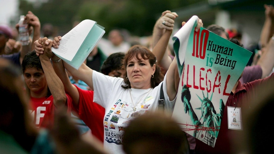 AVON PARK, FL - JULY 23: Rosa Semeraro from Tampa, Florida joins hands with others as they protest against a proposed municipal ordinance that would crack down on illegal immigration July 23, 2006 in Avon Park, Florida. Tom Macklin, the mayor of Avon Park, proposed to fine landlords for renting to illegal immigrants, to take away business permits from any company that knowingly employed illegals, and to locally set English as the official language within Avon Park. The Avon Park City Council is scheduled to take a final vote on the ordinance tomorrow. (Photo by Joe Raedle/Getty Images)