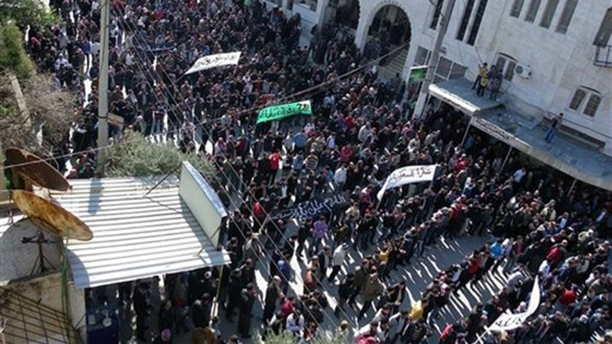 March 2, 2012: Anti-Syrian regime protesters hold up banners during a demonstration in Idlib, Syria.