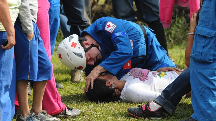 "Mar. 8, 2012: A paramedic attends a woman who fainted while waiting outside the ""El Desespero"" coal mine for news of trapped miners in Angelopolis, Colombia."
