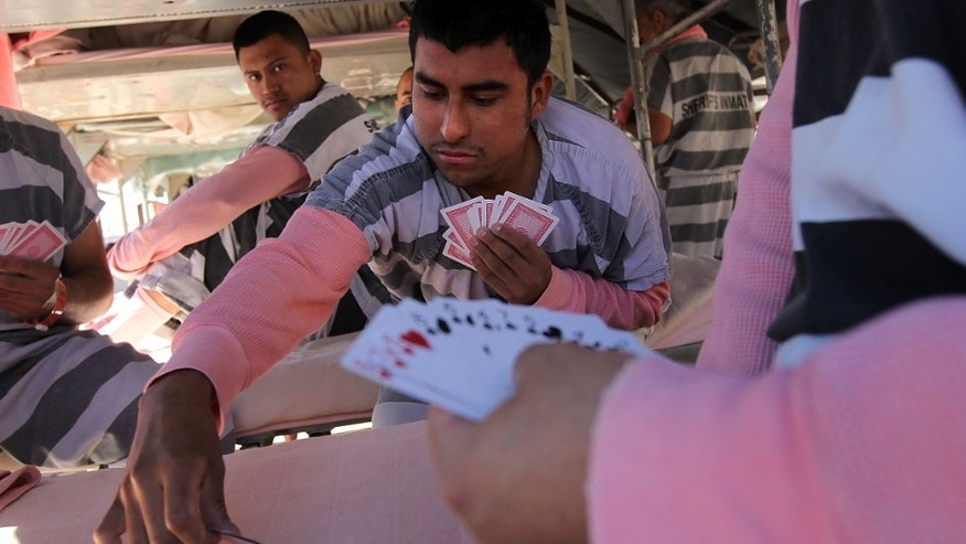 PHOENIX - APRIL 30:  Undocumented immigrants play cards in their tent at the Maricopa County Tent City Jail on April 30, 2010 in Phoenix, Arizona. Some 200 undocumented immigrants are currently serving time in the facility, and most will be deported to Mexico after serving their sentence. The controversial jail is run by Maricopa County Sheriff Joe Arpaio, who has been an outspoken critic of illegal immigration and a supporter of Arizona's new tough immigration law. Prisoners at the facility are fed twice a day, sleep in non-airconditioned tents and are issued striped prison uniforms and pink underwear and socks.  (Photo by John Moore/Getty Images)