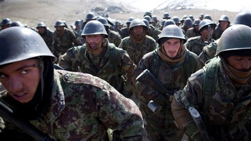March 8: Afghan National Army soldiers walk up a hill as they arrive for a training session at the Kabul Military Training Center, KMTC, on the outskirts of Kabul, Afghanistan. The Afghan National Army will be tasked with providing security throughout Afghanistan after the last international troops pull out in 2014.
