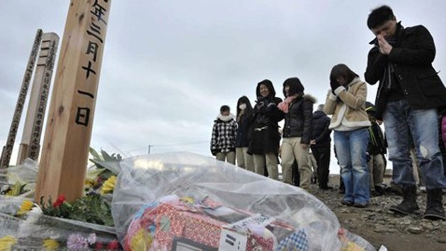 Mar. 11, 2012: People offer prayers to mourn the victims of the March 11, 2011 earthquake and tsunami on a hill in Natori, Miyagi prefecture, Japan.