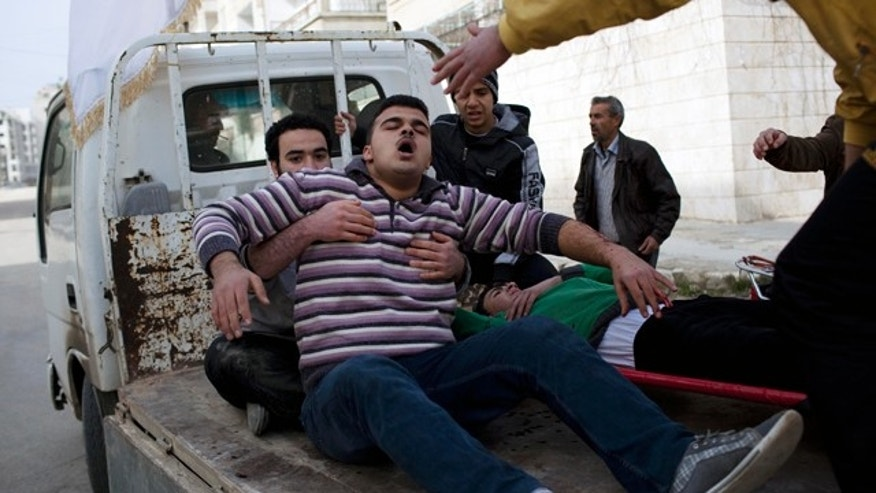 March 10, 2012: Injured men are carried to a hospital during fierce fighting between Free Syrian Army fighters and government troops in Idlib, north Syria.