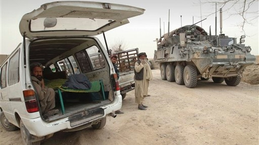 March 11, 2012: An armored military vehicle from the NATO-led International Security Assistance Force (ISAF) is seen at right, as the covered body of a person who was allegedly killed by a U.S. service member is seen.