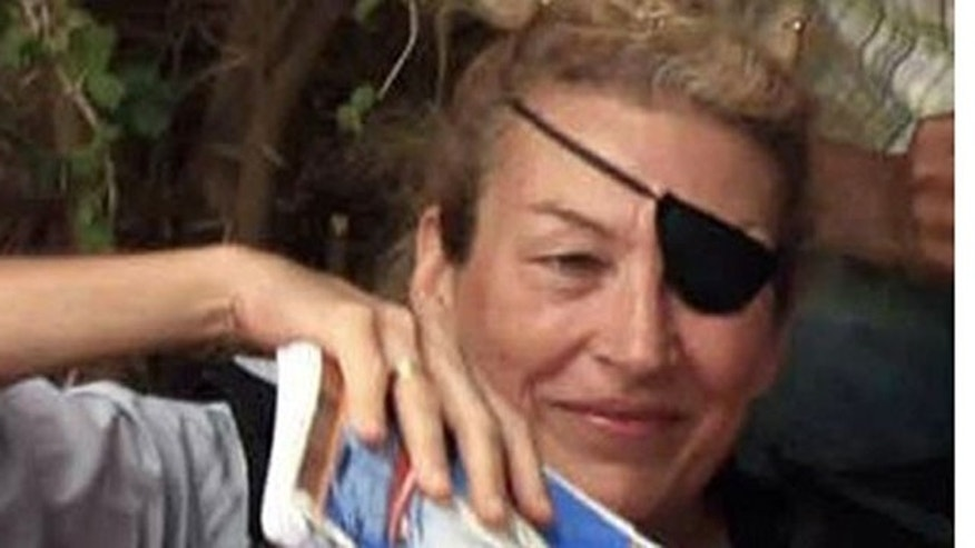 In this June 4, 2011 file photo, journalist Marie Colvin poses for a photograph with Libyan rebels (unseen) in Misrata.