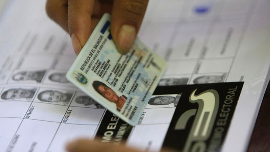 An election worker helps a voter find her name on a voter list during legislative and municipal elections in Suchitoto, El Salvador, Sunday March 11, 2012. (AP Photo/Luis Romero)