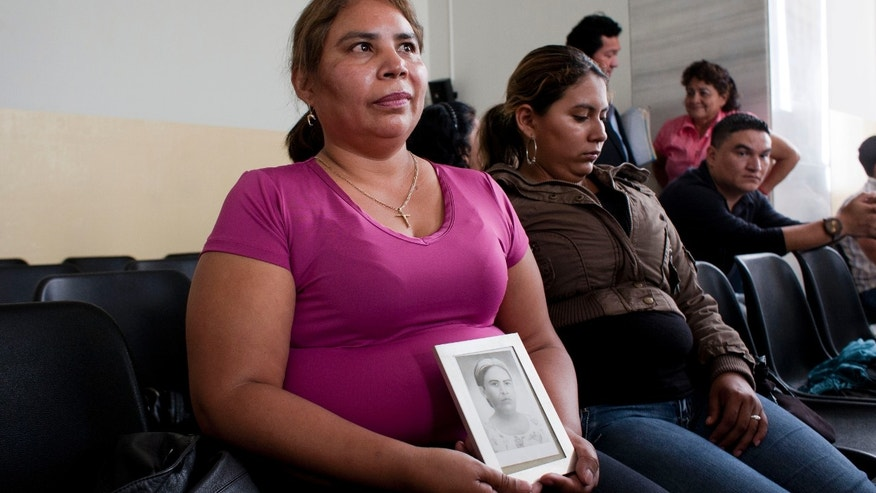 "Felicita Romero, left, holds an image of her mother Natividad Ramirez, a victim of the Dos Erres massacre,  as she attends the trial of Pedro Pimentel Ríos, not in picture, a former member of an elite Guatemalan military force known as the ""kaibiles,"" at a court in Guatemala City, Monday. (AP Photo/Moises Castillo)"