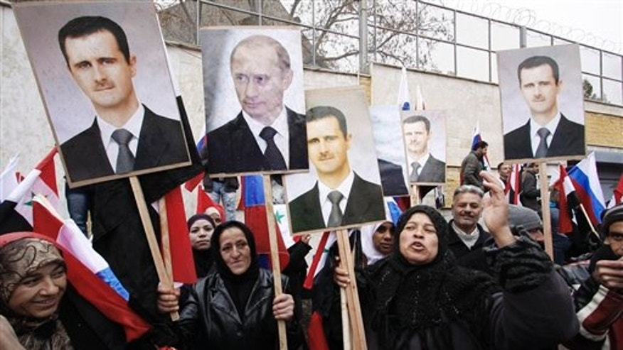 March 4: Syrians hold photos of Syrian President Bashar Assad and Russian Prime Minister Vladimir Putin during a pro-Syrian regime protest in front of the Russian Embassy in Damascus, Syria.