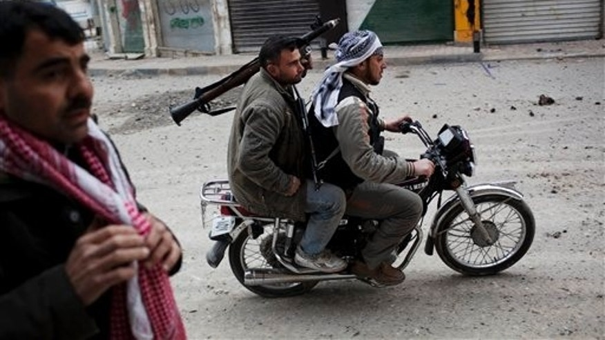 March 11, 2012: In this file photo, Free Syrian Army fighters ride a motorbike to approach Syrian Army tanks in Idlib, north Syria. In the previous days, troops had encircled Idlib, and tank shells pounded the city from dawn until evening. Rebels dashed through the streets, taking cover behind the corners of buildings as they clashed with the troops.