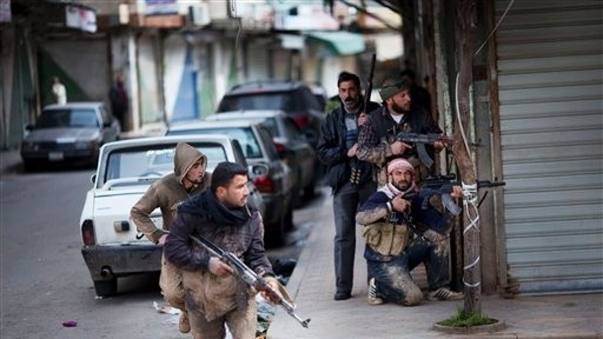 In this Sunday, March 11, 2012 photo, Syrian rebels take position during clashes with government forces in Idlib, north Syria. (AP Photo/Rodrigo Abd)